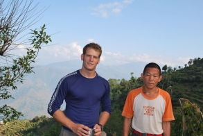 My porter and I taking a few minutes rest and admiring the view of the Himalayas in the background.